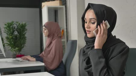 culto : Young beautiful sad girl in black hijab sits in the office and speaks on the smartphone. Unhappy 60 fps