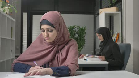 feminism : Young beautiful girl in a pink hijab writes in a notebook, learns, study. Arab women in the office 60 fps Stock Footage