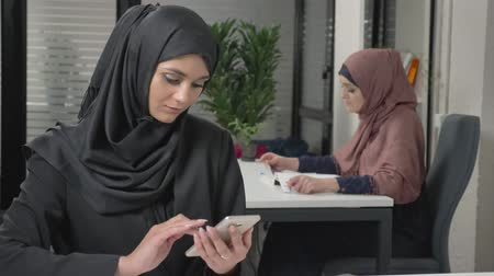 kult : Young beautiful girl in black hijab with headset answers a call center. Arab women in the office. 60 fps