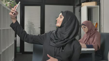 культ : Young beautiful girl in hijab sits in office and makes selfie. Young beautiful girl in hijab sits in office and makes selfie. Arab women in the office. 60 fps