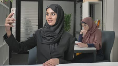 arabesco : Young beautiful girl in hijab sits in office and makes selfie. Shows a greeting sign in the video chat. Arab women in the office. 60 fps