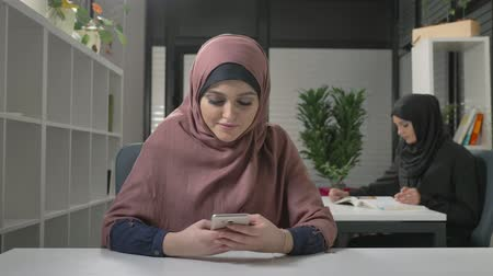 kult : Beautiful young girl in red hijab sits in office and uses smartphone. Arab women in the office. 60 fps