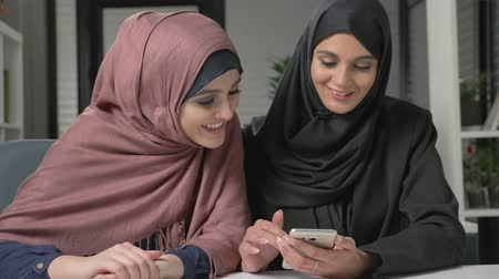 İslamiyet : Two young beautiful girls in hijabs are sitting in the office and using a smartphone. Look funny photos. Laughing. 60 fps
