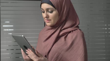 culto : A young beautiful girl in pink hijab uses a tablet, speaks in a video chat, greeting. 60 fps