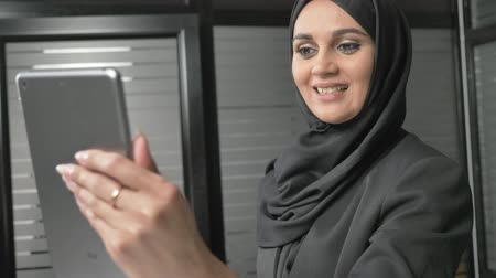культ : A young beautiful girl in black hijab uses a tablet, speaks in a video chat, waves her hand, greeting. 60 fps