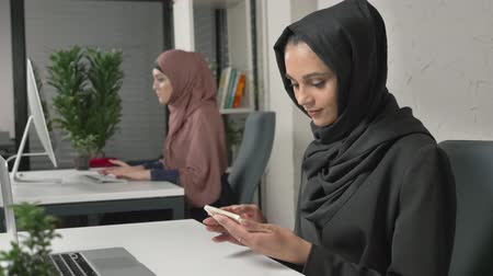 culto : Young beautiful girl in black hijab sits in office and uses smartphone. Girl in black hijab in the background. Arab women in the office. 60 fps