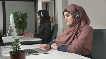 kult : A young beautiful girl in a pink hijab is talking on the headset, answering calls in call center. Arab women in the office. 60 fps