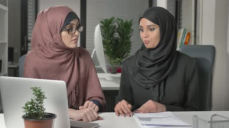 culto : Two beautiful young girls in hijabs sit in the office and discuss schedules, business, dialogue, conversation. 60 fps