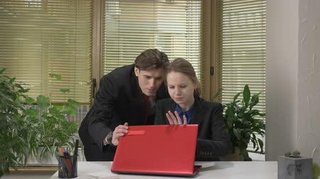 документация : Young guy in a suit flirts with his employee. Trying to close her laptop the girl does not agree. Work in the office concept 60 fps Стоковые видеозаписи