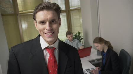 egyéniség : Young man in a suit is smiling and looking at the camera, a man and a girl in the background are working in the office. 60 fps