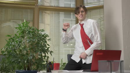 kifejező pozitivitás : Young man in a suit dances in the office,takes off his jacket, makes funny faces, fools around, rejoices. Work in the office concept, 60 fps Stock mozgókép