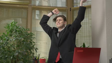 kifejező pozitivitás : Young man in a suit dances in the office, makes funny faces, fools around, rejoices. Work in the office concept 60 fps Stock mozgókép