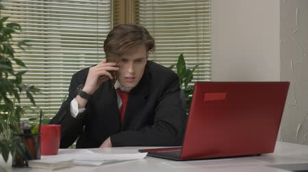 tényleges : Young man in a suit sitting in the office, speaking on the phone, smartphone, showing yes by shaking head, agreement sign. Work in the office concept 60 fps