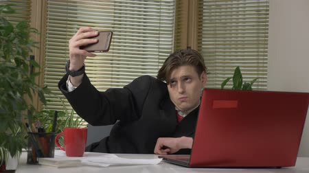 tényleges : Young man in a suit is sitting in the office and making a selfie. Makes funny faces, fools around, rejoicing. Work in the office concept 60 fps Stock mozgókép