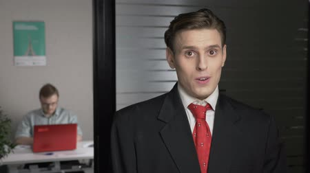 doubt : Young successful man in a suit shows an emotion of doubt, uncertain, portrait. Man works on a computer in the background. 60 fps Stock Footage