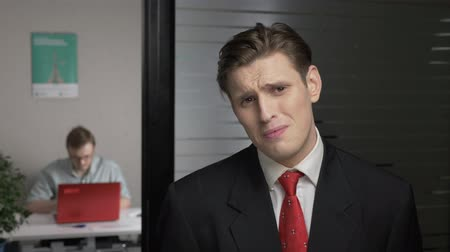 gravata : Young successful man in a suit shows no by shaking head, upset, crying. Man works on a computer in the background. 60 fps