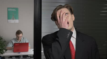 annoyance : Young businessman in suit doing facepalm. Man works on a computer in the background. 60 fps