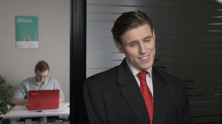 gravata : Young successful man in a suit shows shyness, modesty. Man works on a computer in the background. 60 fps