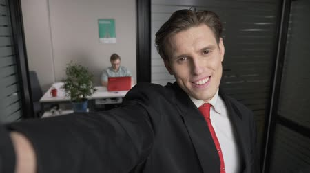 tényleges : Closeup Of young successful businessman in suit Smiling For Selfies. Man works on a computer in the background. 60 fps