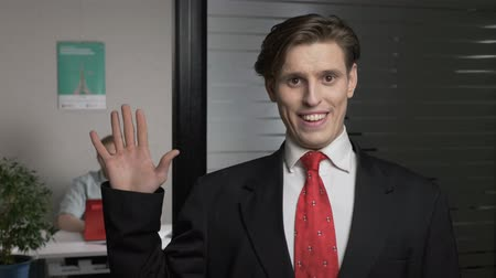 krawat : Young successful businessman in suit waving his hand, gesture of greeting, plastic unnatural smile. Man works on a computer in the background. 60 fps Wideo