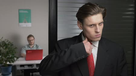 ameaça : Young successful businessman in suit threatens, looks at the camera. Man works on a computer in the background. 60 fps