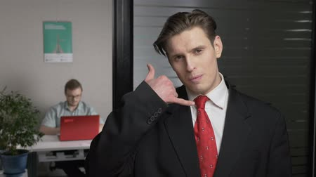 gravata : Young successful businessman in suit showing call me sign, flirting. Man works on a computer in the background. 60 fps