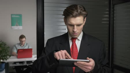 gravata : Young successful businessman in suit looks photo on tablet, using a tablet. Man works on a computer in the background. 60 fps Vídeos