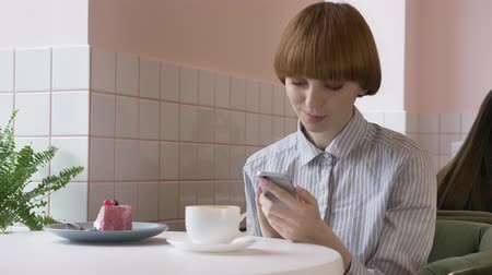 sending : Young beautiful red-haired girl sitting in a cafe, using a smartphone, texting, smiling. 60 fps