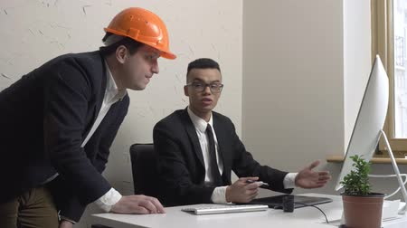 изобретение : Two young businessman, architect, discuss the project and look at the monitor in office. Builders, engineers, concept. 60 fps Стоковые видеозаписи