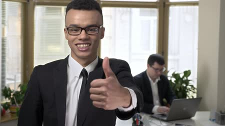 etnia africano : Young successful African businessman looks at the camera and shows a like sign. Man working at the computer in the background. 60 fps