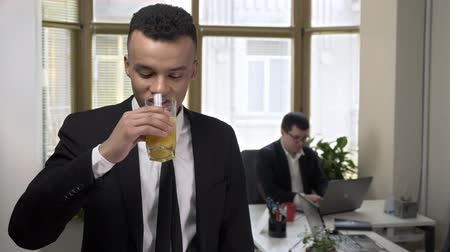 juventude : Young successful African businessman drinks juice from a glass in the office, looking at the camera, portrait, close-up. Man working at the computer in the background. 60 fps Vídeos