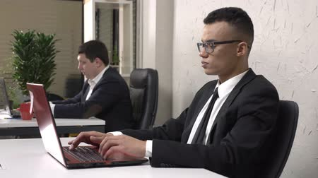 madde : Young successful African businessman wearing glasses is sitting in the office and working on a laptop, takes off his glasses, looks into the camera, smiles and shakes his head, Caucasian man in a suit in the background. 60 fps Stok Video