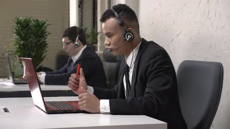 функция : A young successful African man works in the call center, talks on the headset, makes a successful transaction, sells, rejoices in the victory. Caucasian man in suit in the background. Call center concept. 60 fps Стоковые видеозаписи