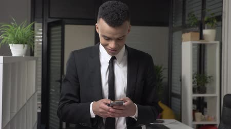 matter : A young successful African male businessman in a suit stands in the office and using a smartphone, texting, typing, smiling Front view. 60 fps Stock Footage