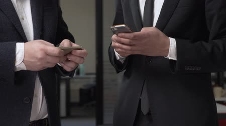 madde : Two businessmen in suits stand in the office and using smartphones. 60 fps Stok Video
