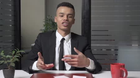 afro amerikan : A young successful African businessman is sitting in the office and talking while looking at the camera. Gestures with his hands 60 fps