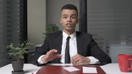 функция : A young successful African businessman is sitting in the office and talking while looking at the camera. Gestures with his hands 60 fps