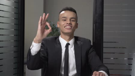 finom : Young successful African businessman in a suit shows a ok sign sitting in the office, smiling. 60 fps Stock mozgókép