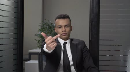 transação : Young successful African businessman in a suit shows a fuck sign sitting in the office, serious face. 60 fps