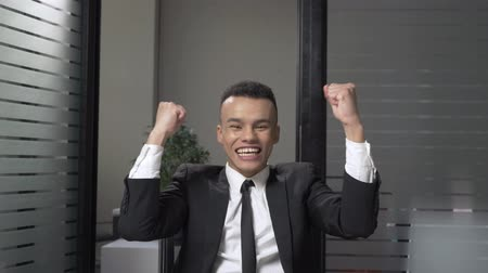 munkatársa : Young successful African businessman in a suit rejoices in victory, raised his fists upwards, sitting in the office, laughing. 60 fps