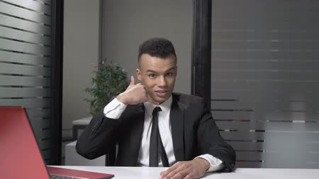 afro amerikan : Young successful African businessman in a suit showing call me sign, sitting in the office. 60 fps