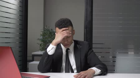 facepalm : Young successful African businessman in a suit showing emotion of disappointment, facepalm, sitting in the office. 60 fps