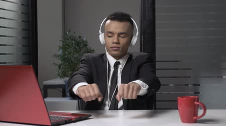функция : Young successful African businessman in suit listening to music on the computer in headphones, dancing in the office. 60 fps