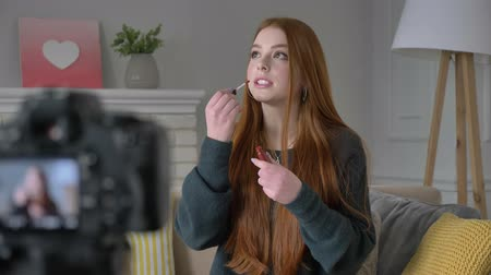 megjegyzés : Young red-haired girl blogger, smiling, talking at the camera, showing a new purchase, cosmetics, lip gloss, make-up concept, home comfort in the background. 60 fps