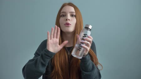 головной убор : Young red-haired girl blogger, smiling, talking at the camera, showing a new purchase, bottle for water, home comfort in the background. 60 fps Стоковые видеозаписи