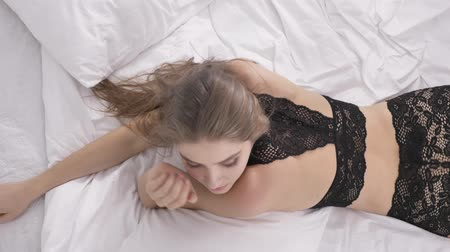 seio : Young caucasian blond girl in sexy black lingerie lies on a bed and looks at the camera, smiling, Portrait, temptation, sunlight in the background, top shot concept 60 fps