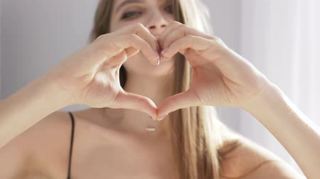 gest : Young beautiful girl shows a heart shape, a sign of love, smiling, laughing, portrait, sunlight, near the window, curtain 50 fps Stock Footage
