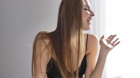 seduzir : Young beautiful sexy girl in black lingerie shows a greeting sign, waving her hand, smiling, sunlight, near the window, curtain 50 fps