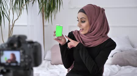 головной убор : Young beautiful Indian girl in hijab recommends an application on a smartphone, smiling, talking at the camera, chroma key, green screen concept. 50 fps