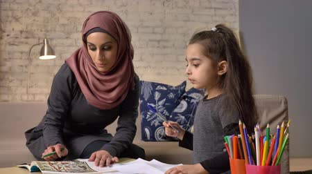 младенчество : Young beautiful mother in hijab doing homework with her little daughter, training, homework, home comfort in the background, colored pencils 50 fps